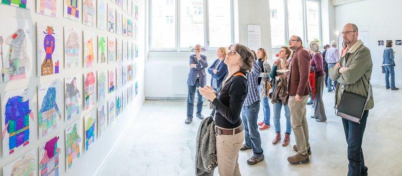 Besucher bei der Ausstellung Zirkus und Jaffa-Krieger betrachten die Zeichnungen an einer Wand