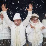 Zwei Frauen und zwei Männer werfen Kunstschnee aus Papierschnipseln in die Luft. Sie lachen und sehen fröhlich aus. Alle tragen dicke weiße Pullover, Mützen und Schals.